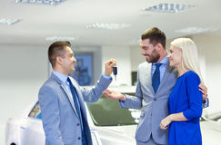 Happy couple with car dealer in auto show or salon. Auto business, sale and people concept - happy couple with dealer giving car key in auto show or salon Royalty Free Stock Photography