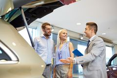 Happy couple with car dealer in auto show or salon Stock Image