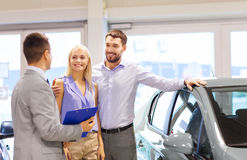 Happy couple with car dealer in auto show or salon. Auto business, car sale, technology and people concept - happy couple with car dealer in auto show or salon Royalty Free Stock Image