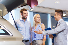 Happy couple with car dealer in auto show or salon Royalty Free Stock Photo