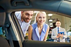 Happy couple with car dealer in auto show or salon. Auto business, car sale, technology and people concept - happy couple with car dealer in auto show or salon Royalty Free Stock Photos