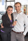 Happy couple with car key in dealership Royalty Free Stock Images