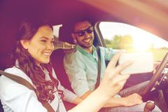 Happy couple in car taking selfie with smartphone royalty free stock images