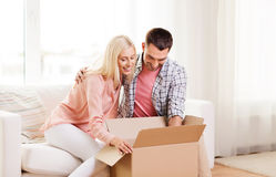 Happy couple with cardboard box or parcel at home Stock Photos