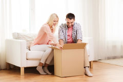 Happy couple with cardboard box or parcel at home Royalty Free Stock Photo
