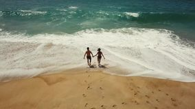 Happy couple carefree running to the water on the beach. Picturesque ocean coast of Portugal stock video footage
