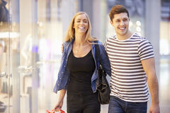 Happy Couple Carrying Bags In Shopping Mall Stock Photos