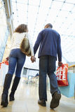 Happy Couple Carrying Bags In Shopping Mall Stock Images