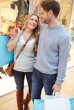 Happy Couple Carrying Bags In Shopping Mall royalty free stock images