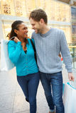 Happy Couple Carrying Bags In Shopping Mall Royalty Free Stock Photography
