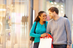 Happy Couple Carrying Bags In Shopping Mall. Looking At Each Other Smiling Stock Photography