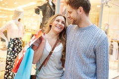 Happy Couple Carrying Bags In Shopping Mall. Looking At Each Other Smiling Royalty Free Stock Image