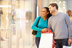 Happy Couple Carrying Bags In Shopping Mall. Looking At Window Display Smiling Stock Images
