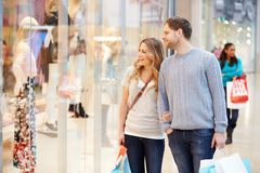 Happy Couple Carrying Bags In Shopping Mall. Looking At Window Smiling Royalty Free Stock Photography