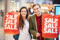 Happy Couple Carrying Bags In Shopping Mall Stock Image