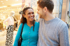 Happy Couple Carrying Bags In Shopping Mall. Smiling At Each Other Royalty Free Stock Photos