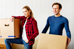 Happy couple carrying cardboard boxes in new home Stock Photo