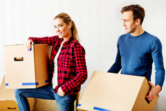 Happy couple carrying cardboard boxes in new home Stock Photos