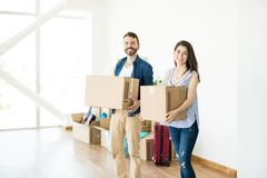 Happy Couple Carrying Cardboard Boxes In New Home. Portrait of happy couple carrying cardboard boxes in new home royalty free stock photography