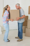 Happy couple carrying cardboard moving boxes Royalty Free Stock Photo