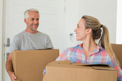 Happy couple carrying cardboard moving boxes Stock Photo
