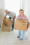 Happy couple carrying cardboard moving boxes Royalty Free Stock Images