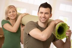 Happy couple carrying carpet together Stock Images