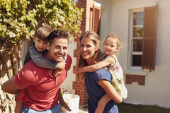 Happy couple carrying children on their backs. Happy father and mother looking at camera while piggybacking their son and daughter. Happy young family of four royalty free stock photo