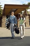 Happy Couple Carrying Golf Bags. Full length of happy couple carrying golf bags walking out of building Stock Photos