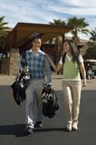 Happy Couple Carrying Golf Bags. Full length of happy couple carrying golf bags walking out of building Royalty Free Stock Photo