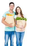 Happy couple carrying grocery bags Stock Photos