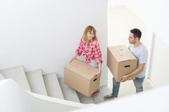 Happy couple carrying moving boxes up stairs in new house Royalty Free Stock Images