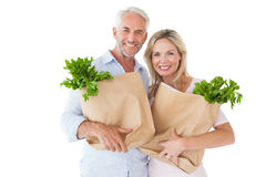 Happy couple carrying paper grocery bags Stock Photography