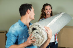 Happy couple carrying rolled up rug Royalty Free Stock Images
