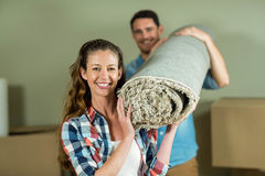 Happy couple carrying rolled up rug Royalty Free Stock Photography