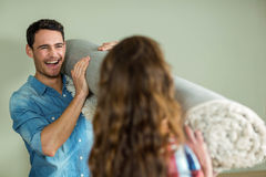 Happy couple carrying rolled up rug Royalty Free Stock Image