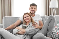 Happy couple with cat. At home Royalty Free Stock Photo
