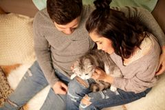 Happy couple with cat at home. Pets, hygge and people concept - happy couple with cat at home royalty free stock images
