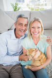Happy couple with cat sitting in living room Royalty Free Stock Images
