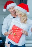 Happy couple celebrating Christmas in Santa hats Royalty Free Stock Photos