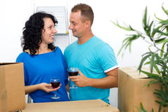 Happy couple celebrating moving to new house with red wine Stock Photography
