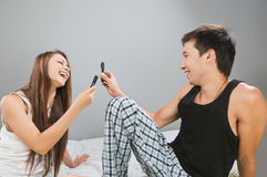 Happy couple with cellulars. Happy young couple with cellulars in bed Royalty Free Stock Photos