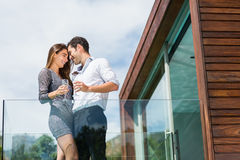 Happy couple with champagne at balcony. Low angle view of happy couple with champagne at balcony in resort Stock Photography