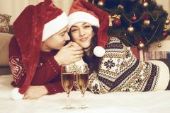 Happy couple with champagne lie near xmas tree and decoration at home. Winter holiday and love concept. Yellow toned. Royalty Free Stock Image