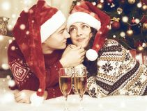 Happy couple with champagne lie near xmas tree and decoration at home. Winter holiday and love concept. Yellow toned. Stock Images