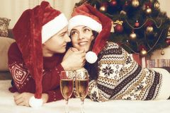 Happy couple with champagne lie near xmas tree and decoration at home. Winter holiday and love concept. Yellow toned. Royalty Free Stock Images