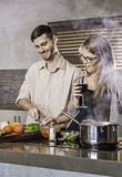 Happy couple chatting and cooking a meal in the kitchen flirting bonding Stock Photo