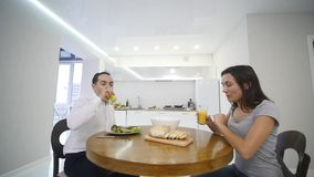 Happy couple chatting and having breakfast together at home in the kitchen stock footage