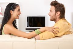 Happy couple chatting on sofa. Side view stock photos