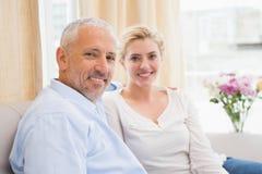 Happy couple chatting on sofa Stock Photo